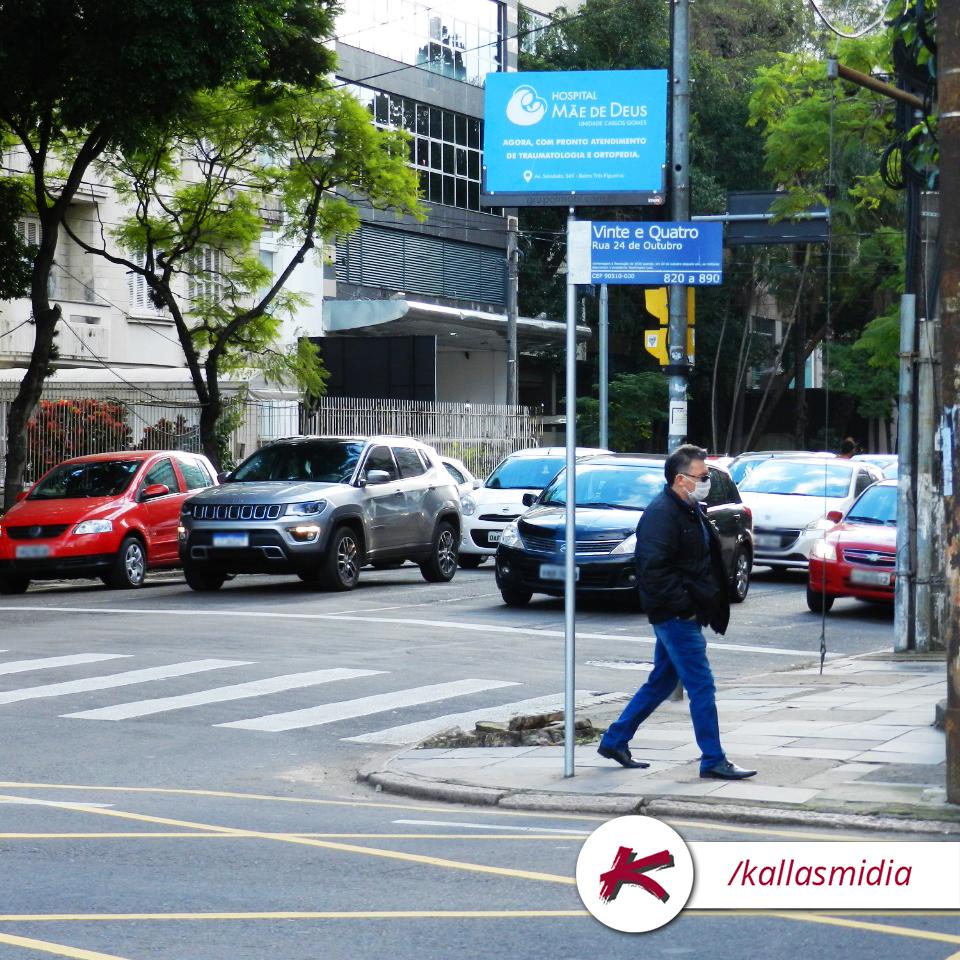 Placa de rua em esquina com homem andando e carros parados.
